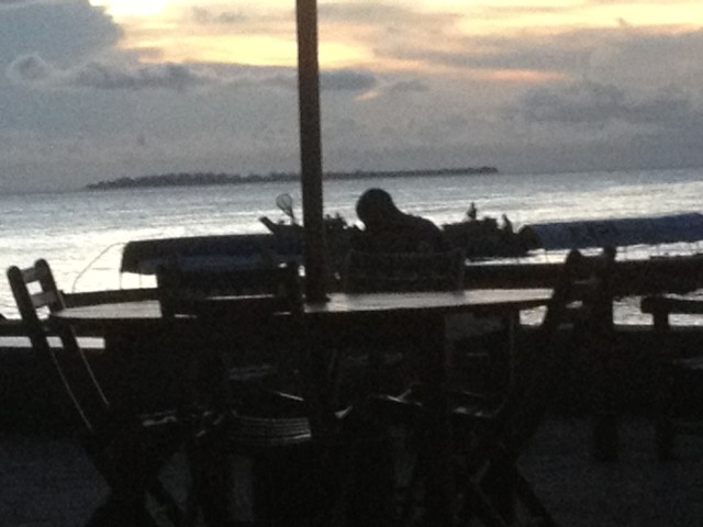 A person checking his phone at sunset. The power had just been out for a few minutes
